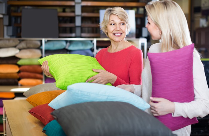 Two women in a store looking at throw pillows in various colors