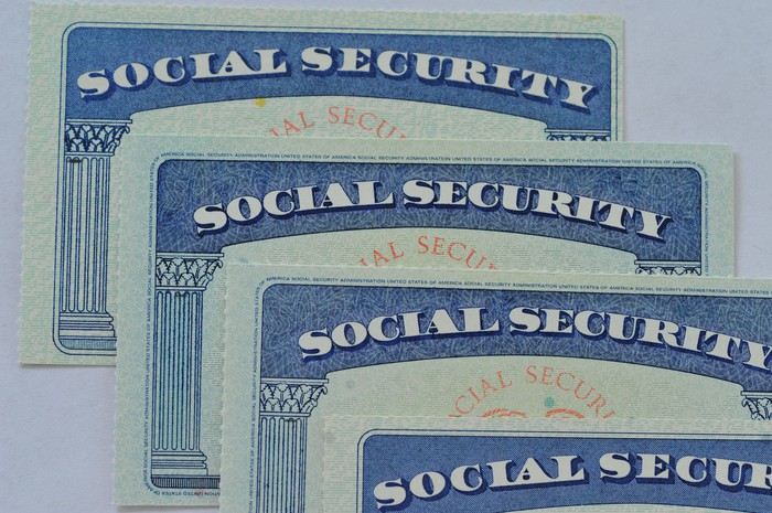 Four Social Security cards each resting on top of the next