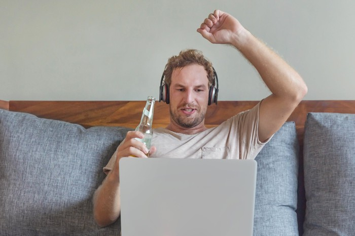 man with headphones on couch streaming sports and drinking a beer