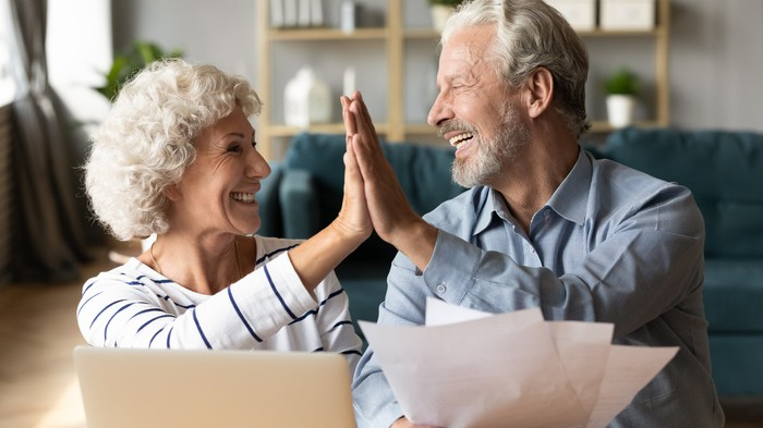 Older couple high-fiving over papers