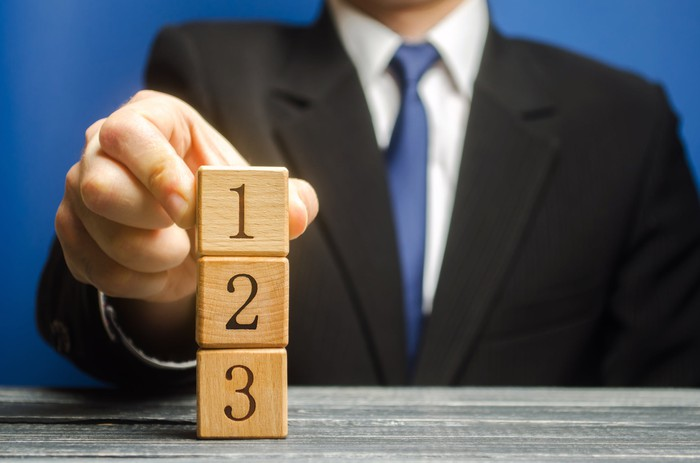 Man in a suit stacking wooden blocks, top-down from 1 to 3.