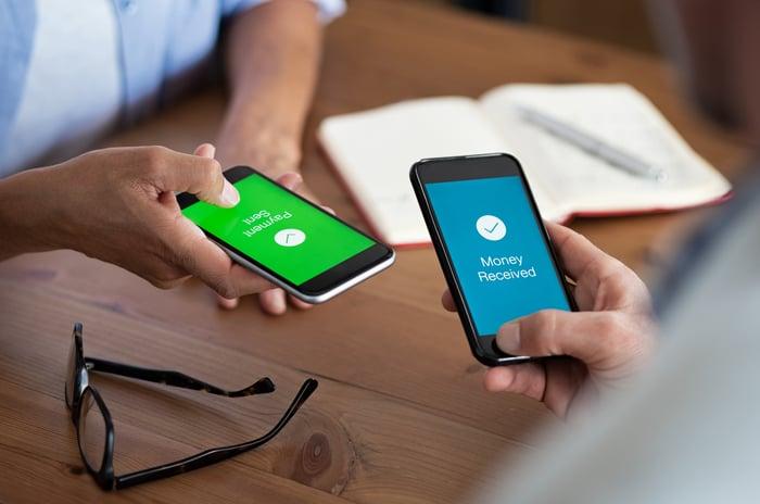 Two people sending money on smartphones.