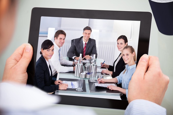 Two hands holding a tablet computer showing a video conference.