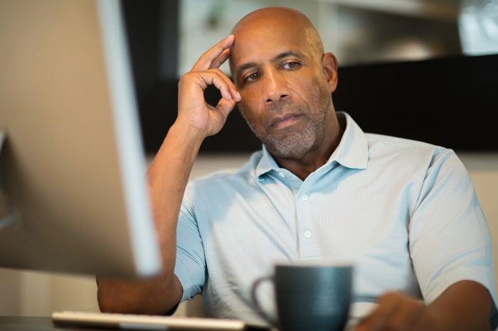 Older man sitting at desk, looking worried.