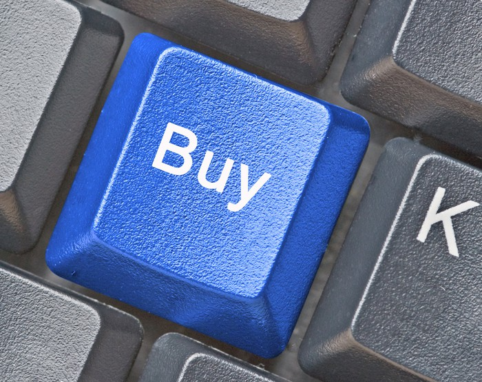 """""""Buy"""" on a blue key surrounded by grey keys on a keyboard."""