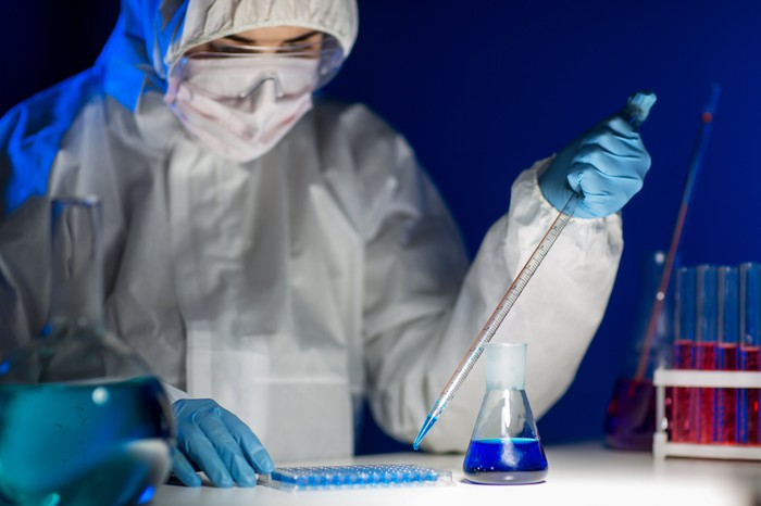 A pharmaceutical lab technician using a pipette to add liquid samples to a tray.