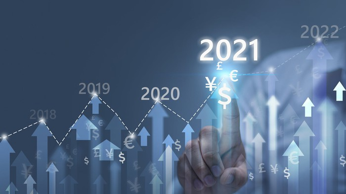 "A man touches an illuminated ""2021"" on top of rising arrows and currency symbols."