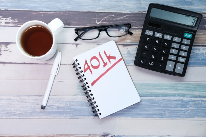"A notebook on a table with the word ""401(k)"" written in red."