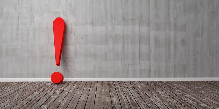 A large, red exclamation point sits on a wood floor and leans against a wall.