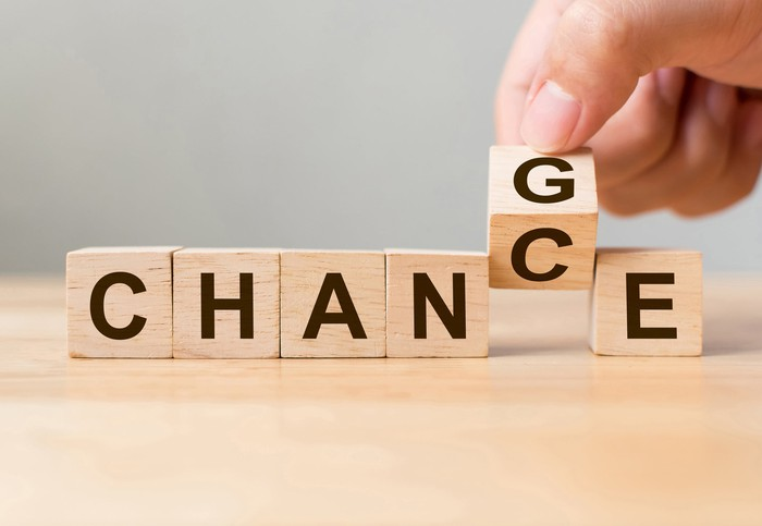 6 wooden blocks spell out the word CHANCE. A hand is turning the second C over to a G.