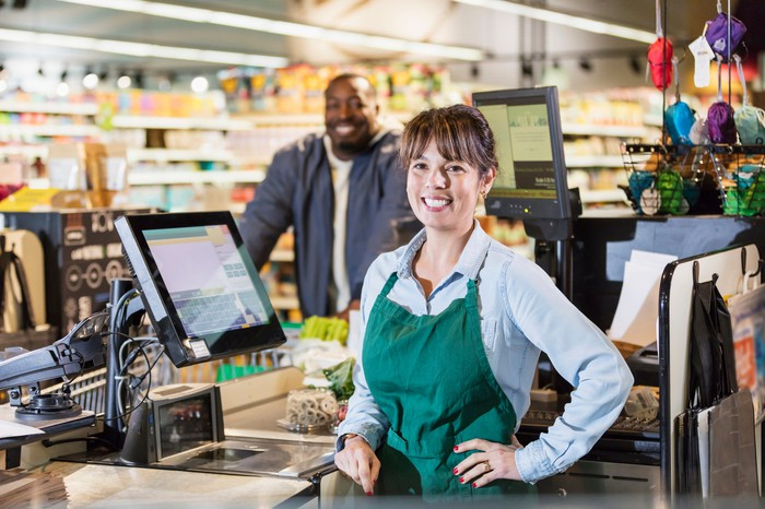 Part-time worker standing at the cash register smiling.