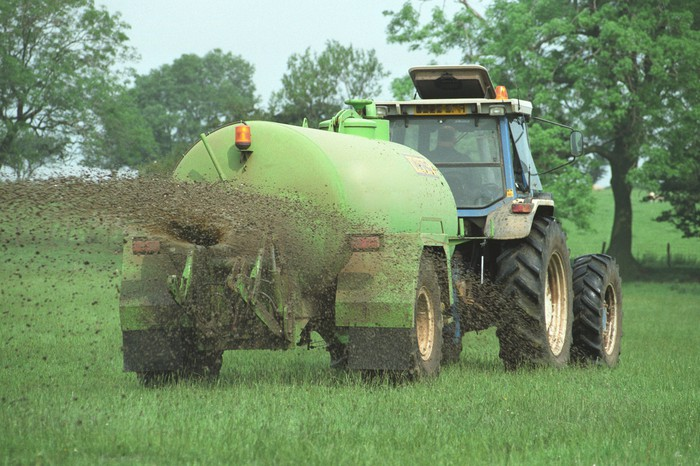 tractor spreading fertilizer in a grass field