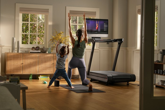 A mother and child work out in their home gym, following a yoga instructor on the treadmill's screen.