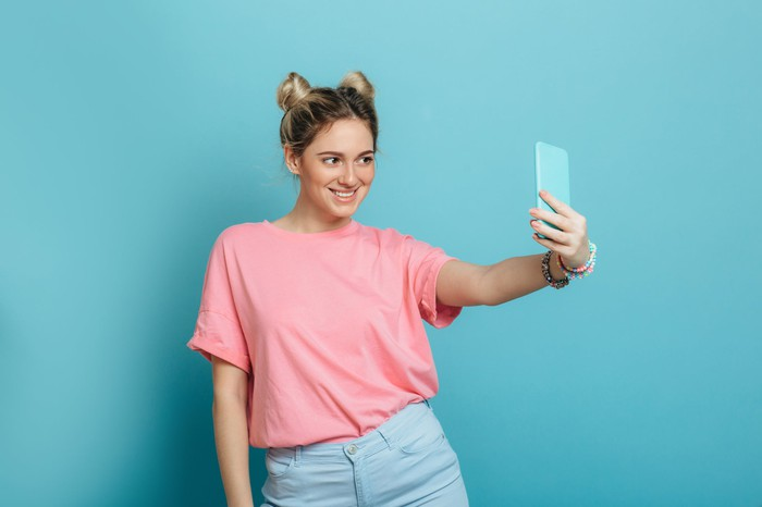 A young woman takes a selfie with her phone.