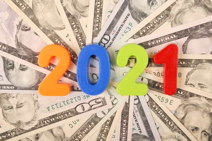 The year 2021 spelled out in multicolored blocks that are set atop a fanned pile of cash.