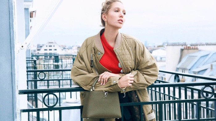 A woman holding an LV Capucine bag.