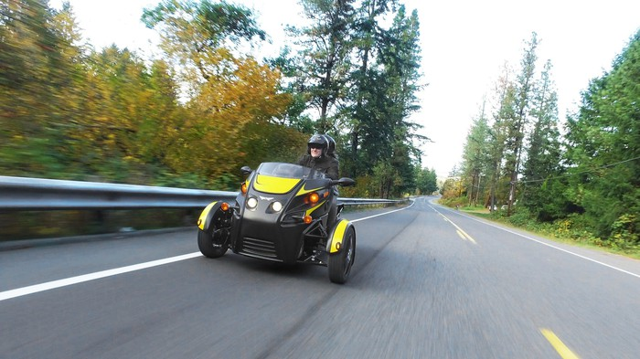 Two people riding on an Arcimoto Roadster.
