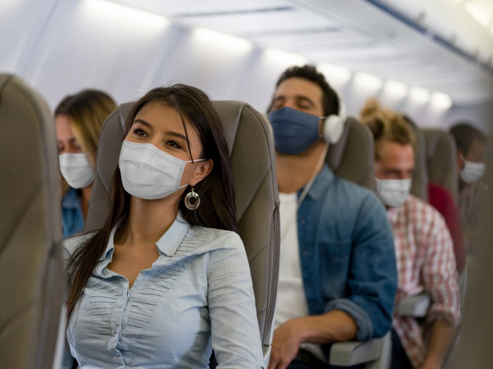 A woman wears a face mask while traveling on an airline during the COVID-19 pandemic.