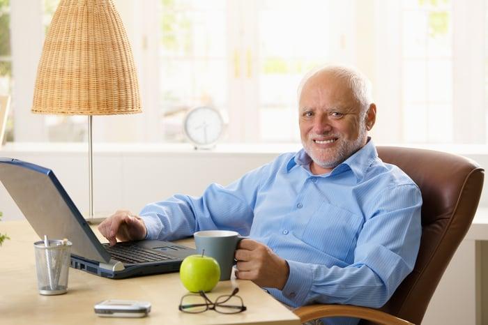 Smiling older man holding mug while typing on laptop