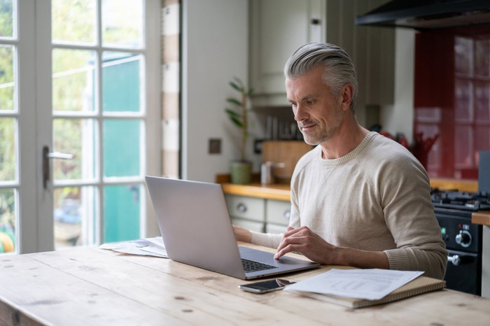 A middle aged man smiles at his laptop at home.