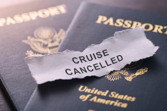 The words cruise canceled are typed on a torn piece of paper, which is on top of two passports.