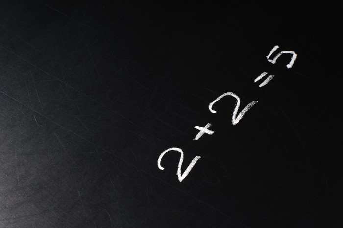 Two plus two equals five drawn on a chalkboard.