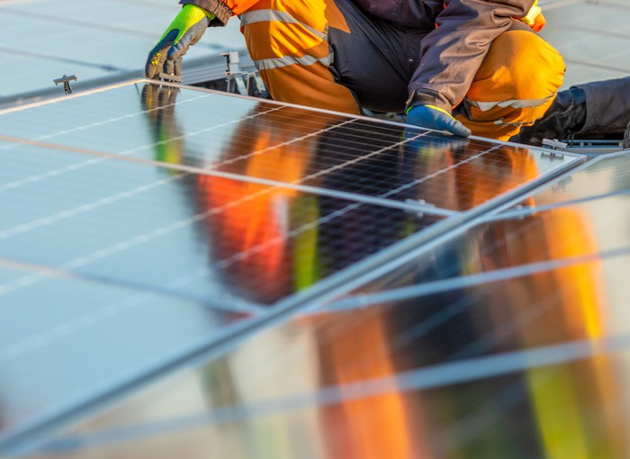 A worker installs a solar panel on a rooftop.