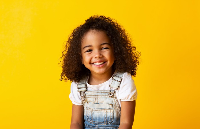 Little girl smiling in front of yellow background.