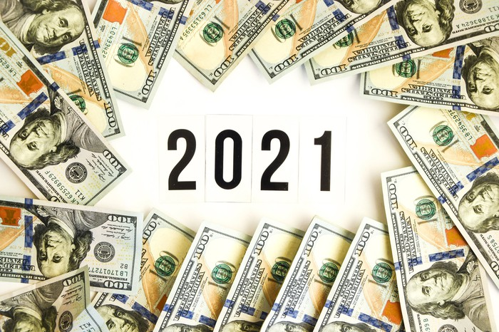Dollar bills arranged in a circle with 2021 in the middle.