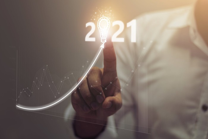 A person pointing to an image of 2021 with a light bulb in the place of the zero next to a line trending upward