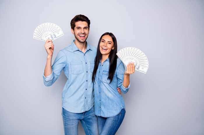 Smiling young man and woman holding cash in their hands