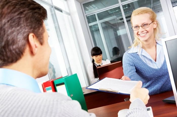 Woman handing form to financial advisor.