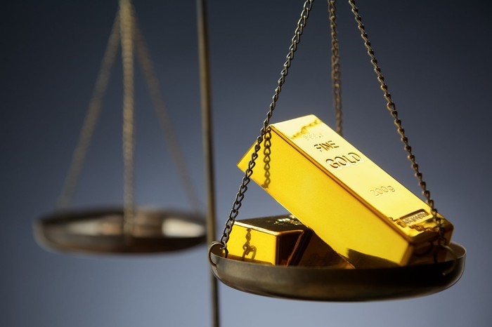 A scale, with bars of gold on one side and bitcoin tokens on the other.