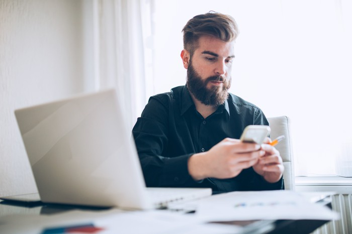 Man sits in front of laptop and various papers, scrolling through phone with pencil in hand