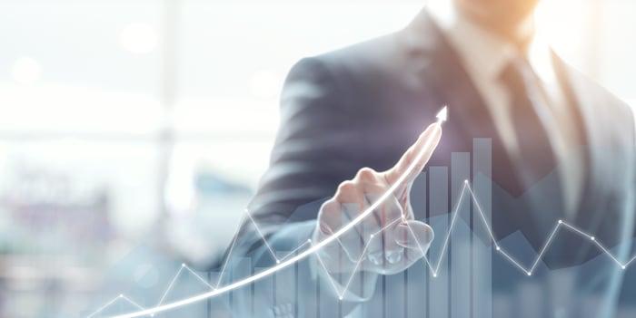 A businessman draws an upward arrow over a bar chart displayed on a transparent touchscreen.