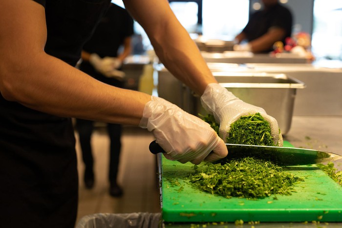 Chipotle Mexican Grill worker cutting cilantro.