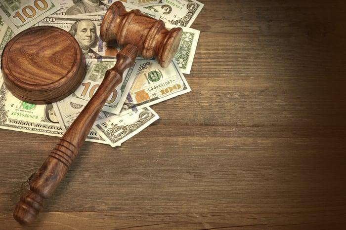 A judge's gavel lies atop a pile of $100 bills.