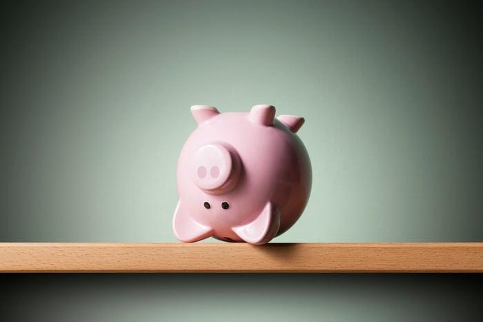 Upside down piggy bank on a shelf.