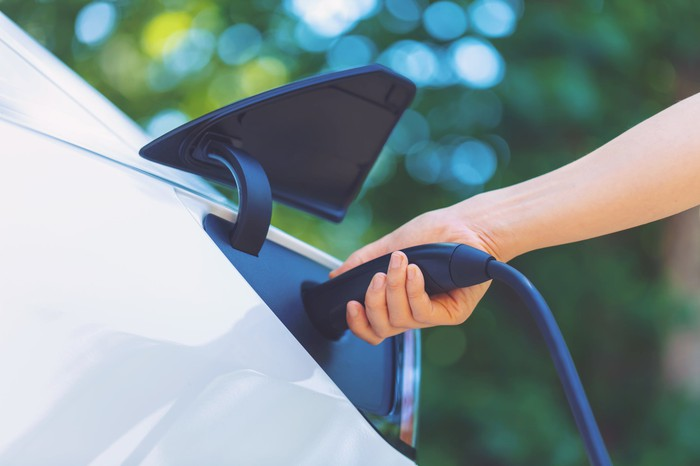 Person plugging in an electric vehicle to charge