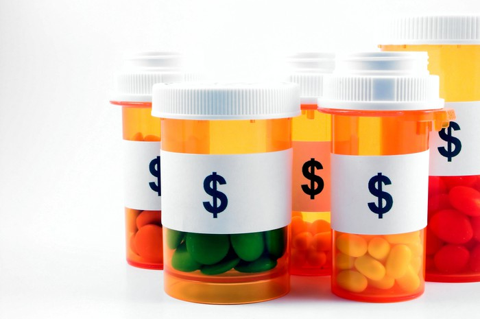 An assortment of prescription drug bottles labeled with dollar signs.