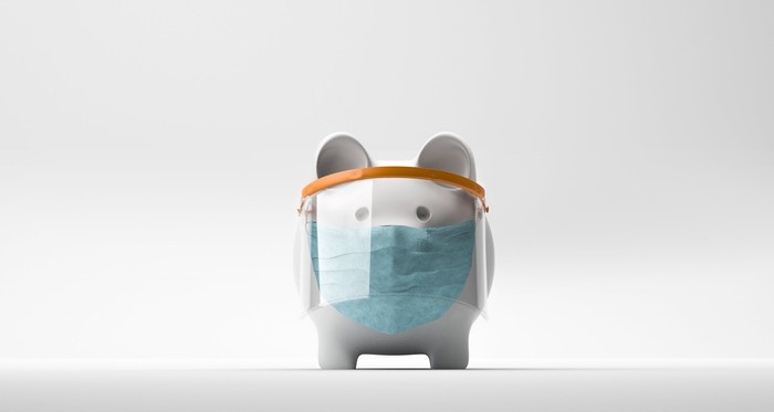 Piggy bank wearing a face shield over a surgical mask