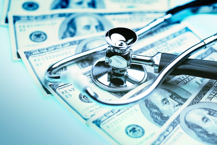 A stethoscope placed atop neatly fanned one hundred dollar bills.