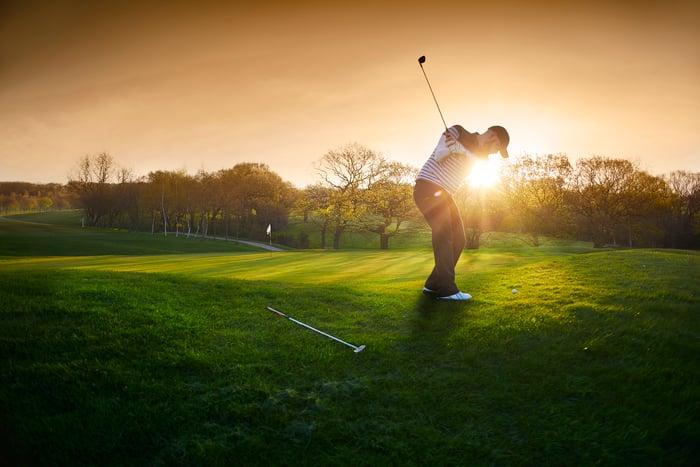 A golfer swings a club near a green as the sun sets.