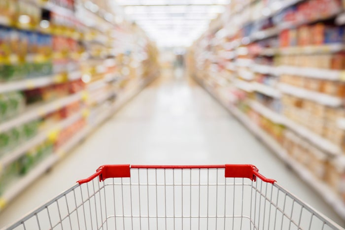 A grocery cart in a supermarket aisle.