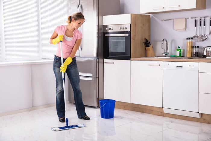 A young woman mopping a kitchen floor.