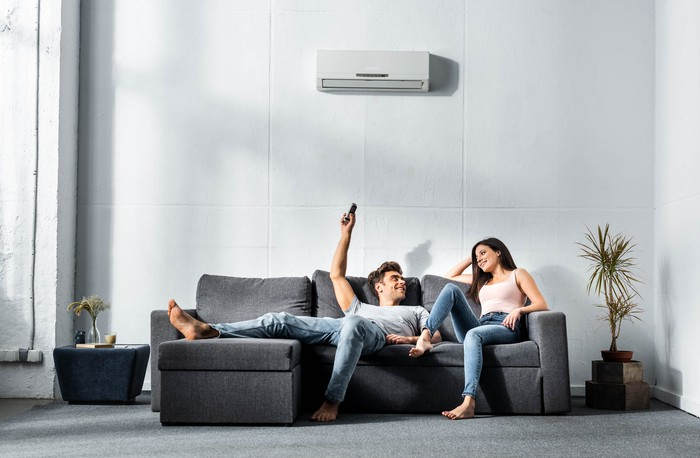 Couple seated on a sofa beneath an air conditioner