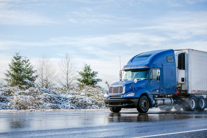 A refrigerated semi truck driving on a highway in winter.