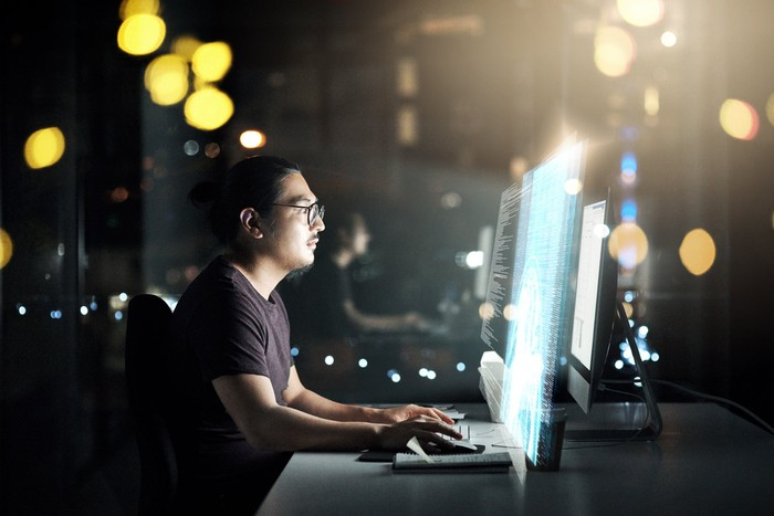 Man coding in a dark room on a computer with a bright screen.