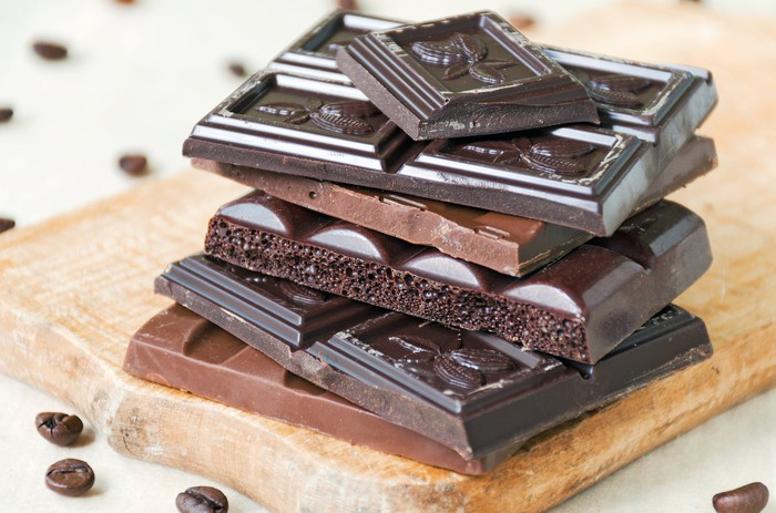 Dark chocolate bar pieces stacked up on a wooden kitchen board.