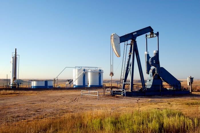An oil pump next to some storage tanks.